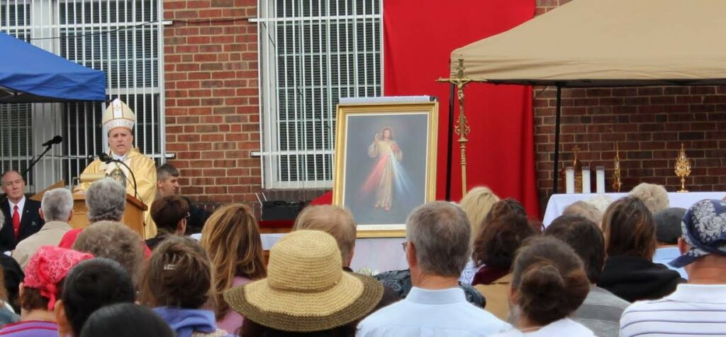 Archbishop Samuel Aquila speaks at St. Joseph Polish Church's first Divine Mercy Sunday celebration with relics of St. Faustina and St. John Paul II.