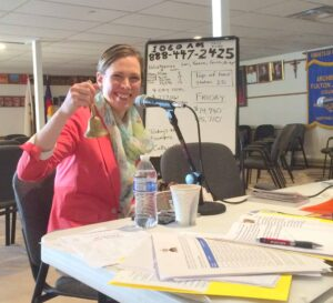 Karna Swanson, executive director of the Office of Communications, rings a bell during a KRCN pledge drive to support the Catholic radio station.