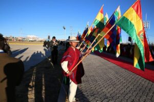 People holding flags while waiting for the pope to arrive at an airport in El Alto, Bolivia on July 8.