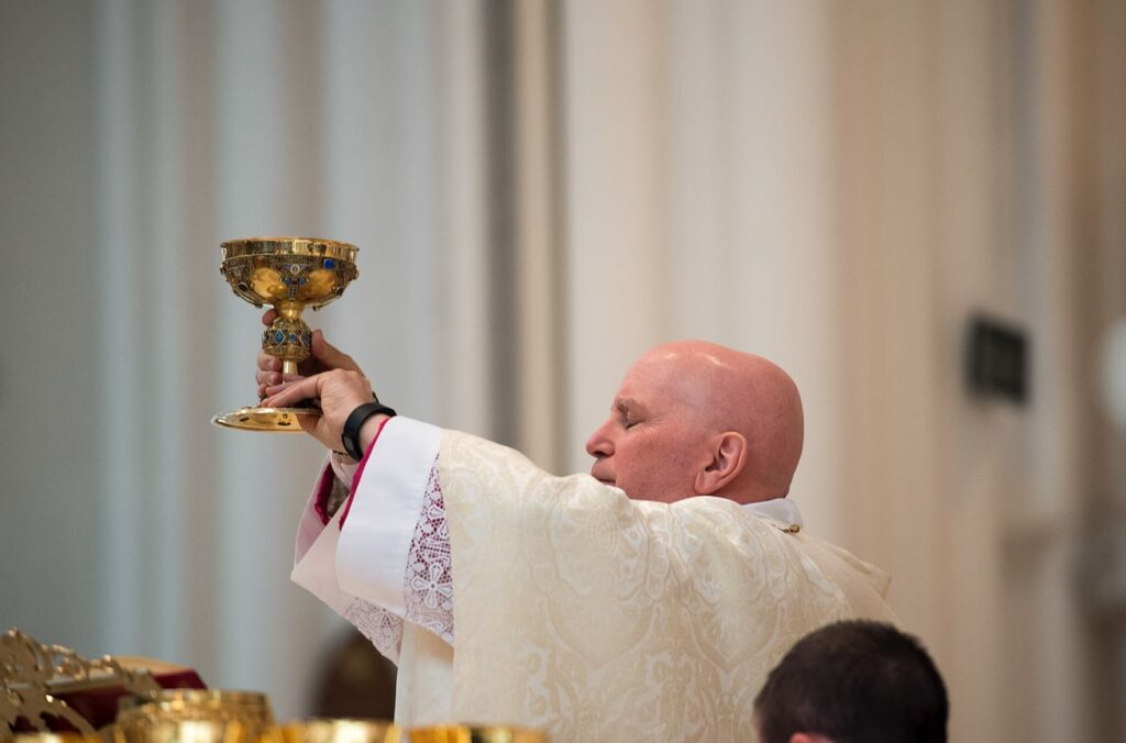 DENVER, CO, March 23, 2016 - Archbishop Samuel J. Aquila presents the wine for consecration during the Chrism Mass at the Cathedral Basilica of the Immaculate Conception. (Photo by Dan Petty/A&D Photography)