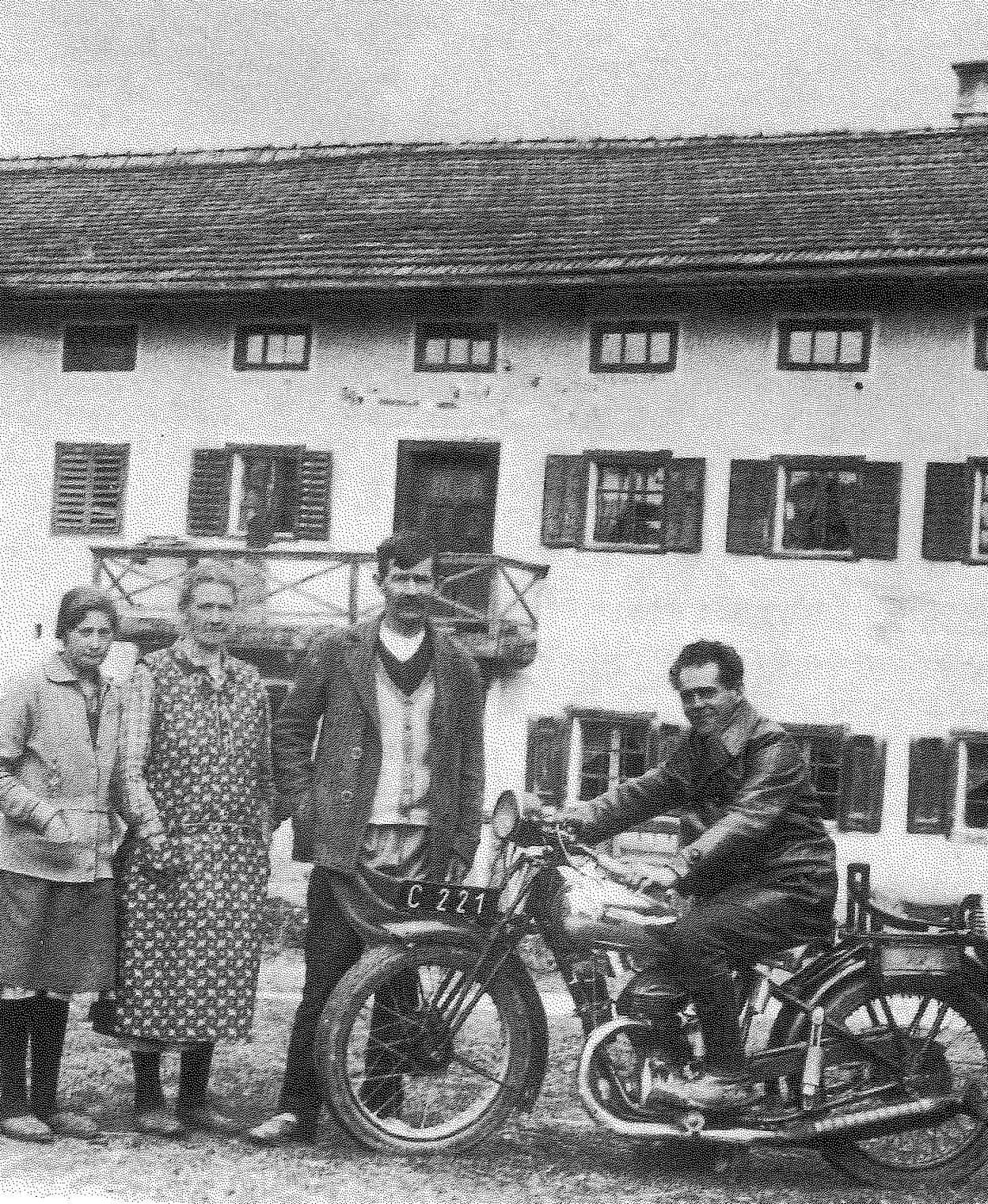 Franz Jagerstatter poses on his motorcycle. From right to left: Franz Jagerstatter; his stepfather, Heinrich Jagerstatter; his mother, Rosalia Jagerstatter; and Aloisia Sommerauer, Franz's cousin and foster sister. / Styria Verlag. Used with permission.