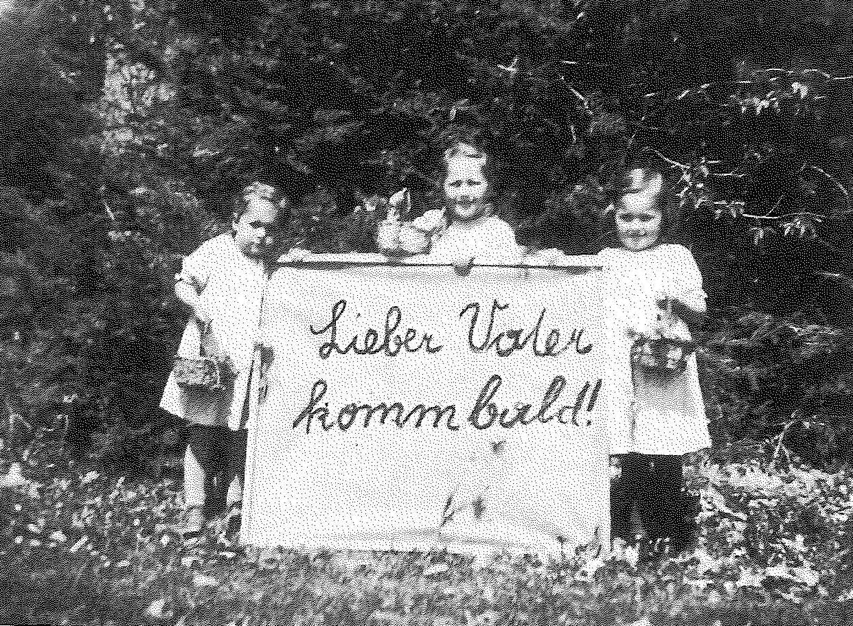 """Easter 1943: Franz Jagerstatter's daughters; Loisi, Rosi, and Maria, holding a sign that reads, """"Dear Father, come [home] soon."""" Franz was in jail in Linz and was later executed./ Styria Verlag. Used with permission"""