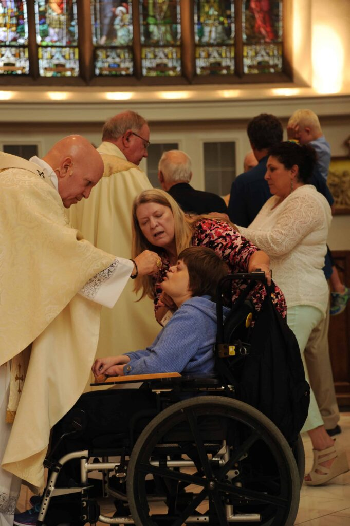 Archbishop Aquila hosts gives a participant in the Special Education Mass Holy Communion. Students and their families were all invited to attend. (Photo by Bernard Grant/Denver Catholic)