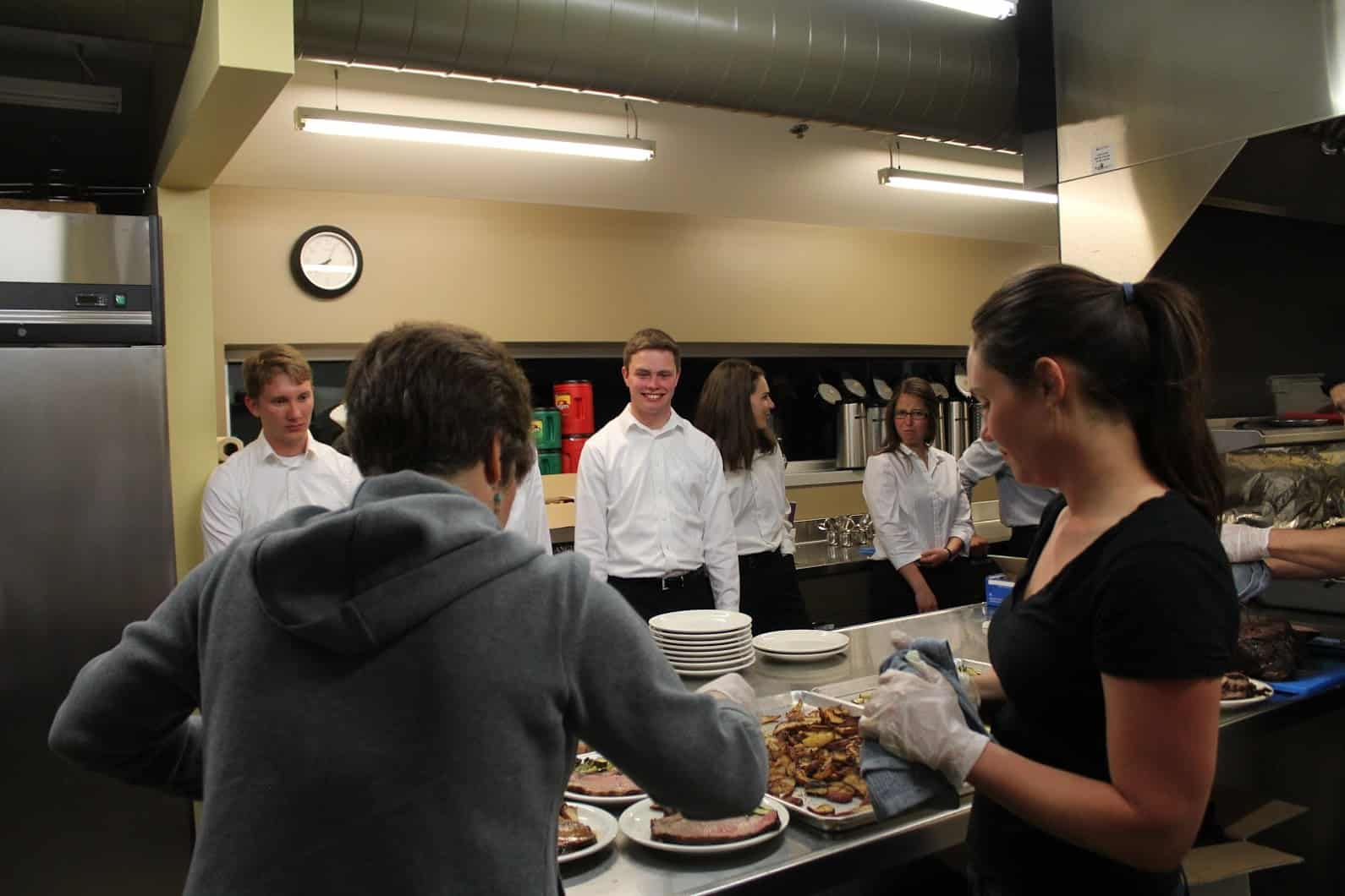 Students at Colorado School of Mines prepare to serve dinner to alumni members of the community. Professor Darrin Muggli also gave a talk on the importance of being a well-formed Catholic engineer. Photo provided.